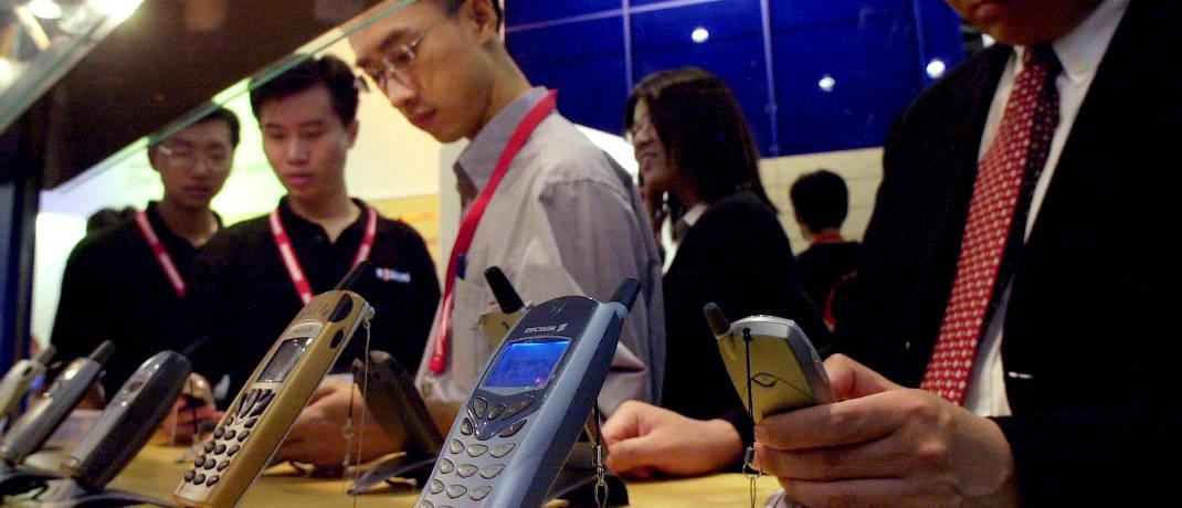 Besucher sehen sich die neuesten Ericsson-Telefone auf der CommunicAsia im Jahr 2001 an: Das Unternehmen warnte (wie einige Konkurrenten auch) in dem Jahr davor, seine Gewinnprognose nicht erfüllen zu können.