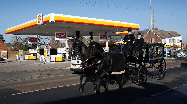 Eine Pferdekutsche passiert auf dem Weg zu einer Beerdigung eine Tankstelle der Royal Dutch Shell in der Nähe des sündenglischen Basingstoke