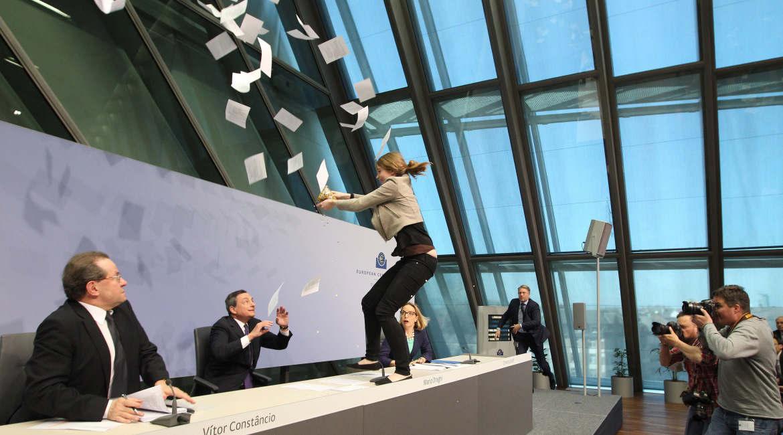 Während einer Pressekonferenz springt eine Aktivistin vor EZB-Chef Mario Draghi auf den Tisch