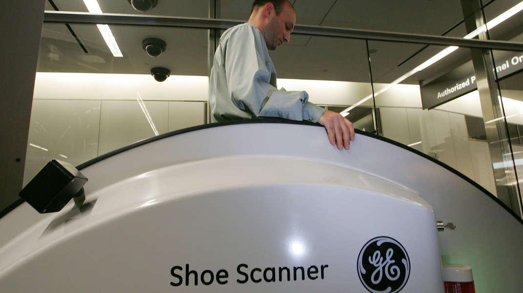 Mitarbeiter von General Electric führt im Jahr 2005 den Prototyp eines Schuh-Scanners für Flughäfen vor