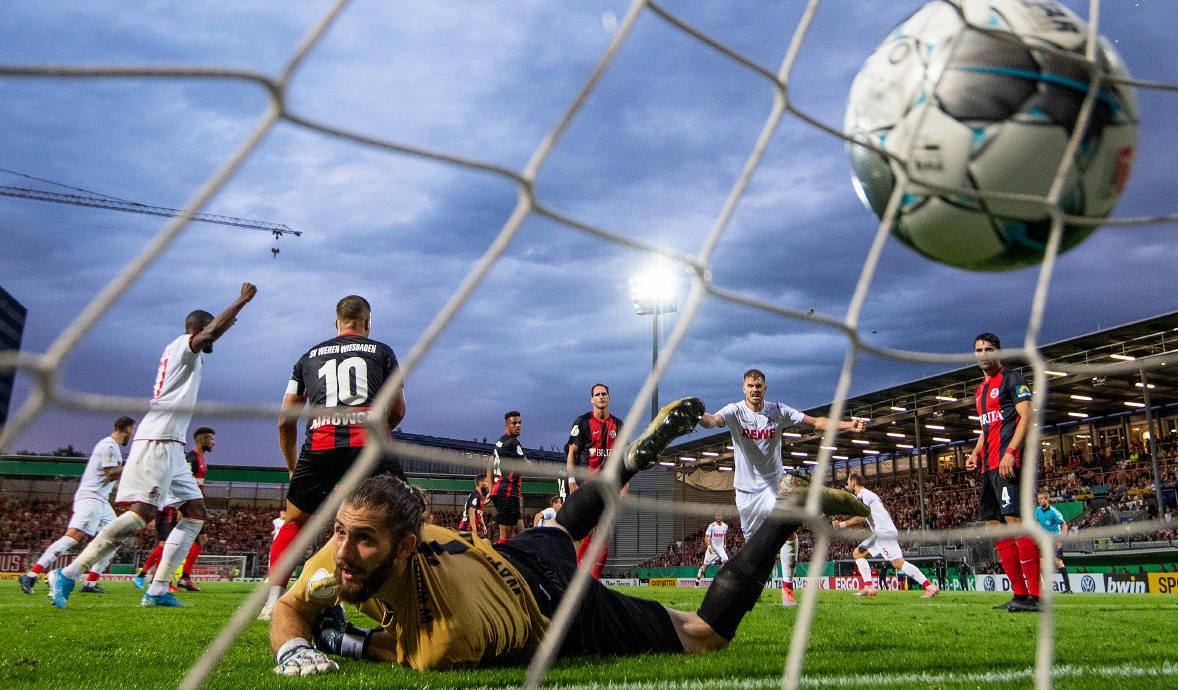 Torhüter Lukas Watkowiak schaut dem Ball hinterher, den ihm Köln-Spieler Louis Schaub gerade eingeschenkt hat: Das DFB-Pokal-Spiel endete 3:3 nach regulärer Spielzeit. Das Elfmeterschießen gewann Köln.