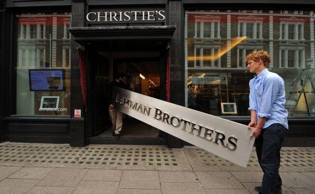 Mitarbeiter des Auktionshauses Christie's tragen ein<br>Lehman-Brothers-Schild. Der Untergang der Investmentbank<br>im September 2008 war einer der H&ouml;hepunkte der globalen<br>Finanzkrise. Foto: Getty Images