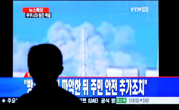 Ein Fernsehzuschauer beobachtet die Explosion des<br>Atomreaktors Fukushima 1. Foto: Getty Images