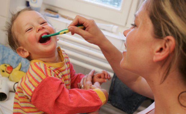 Junge Mutter beim Zähneputzen mit ihrem Kleinen: Für junge Eltern können die Kosten für das Kind problematisch werden. Foto: Getty Images
