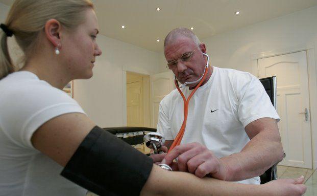 Ein Arzt misst den Blutdruck einer Patientin: Eine Gesundheitsprüfung fällt bei der betrieblichen Krankenversicherung nicht an. Foto: Getty Images