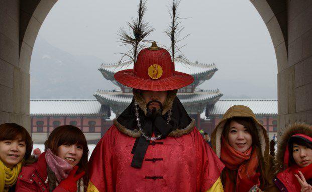 Touristen posieren mit einem als Torwächter verkleideten Schauspieler vor dem Gyeongbokgung Palast in Seoul: Der südkoreanische Markt konnte sich im dritten Quartal wesentlich besser behaupten als andere Schwellenmärkte. (Bild: Getty Images)
