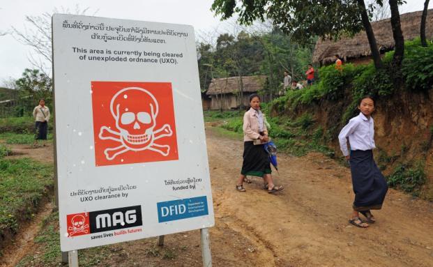 Dieses Schild in Laos warnt vor explosiven Minen im Boden. Geht es nach manchen Parteien, solle die Finanzierung der Kriegsgeräte verboten werden. (Foto: Getty Images)