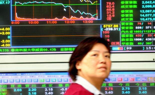 Frau vor einer Kursanzeige in Taiwan, einem der zehn untersuchten Schwellenländer (Foto: Getty Images)