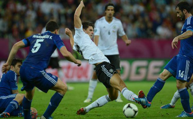 Mario Gomez (Mi.) und der griechische Mittelfeldspieler Giorgos Fotakis (re.) im EM-Viertelfinale Deutschland gegen Griechenland. Quelle: AFP/Getty Images