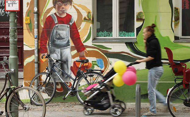 Junge Mutter spaziert mit ihrem Baby an einer Berliner Kindertagesstätte vorbei: Ab 1. August 2013 steht jedem ein- bis dreijährigen Kind per Gesetz ein Kita-Platz zu. Kritiker glauben, dass es viel zu wenige Kitas und Erzieher gibt, um das Gesetz umzusetzen (Foto: Getty Images)
