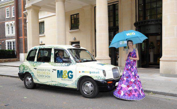 Fahrzeug mit Werbeaufdruck und Model im Blumenkleid anlässlich der Londoner Gartenschau Chelsea Flower Show, bei der M&G als Sponsor auftritt