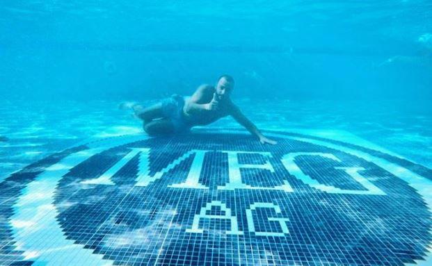 Mehmet Göker beim Inspizieren des MEG-Logos in seinem Pool. Bild: privat/FinanzBuch Verlag
