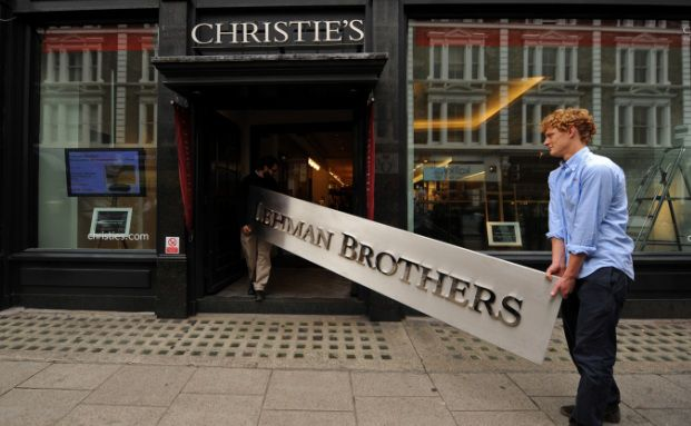 Mitarbeiter des Auktionshauses Christie's tragen ein Firmenschild der Pleite-Bank Lehmann Brothers herein: Seit der Finanzkrise achten vermögende Familien noch mehr auf die Sicherheit ihrer Kapitalanlagen (Foto: Ben Stansall (AFP / Getty Images))