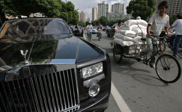 Ein Fahrradfahrer überholt einen Rolls Royce in Shanghai. Armut und Reichtum liegen in China oft nah beieinander. Foto: Getty Images
