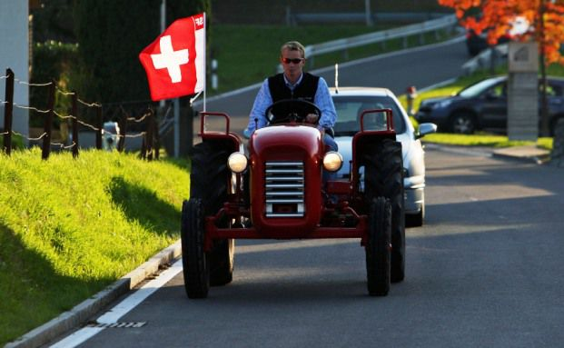 Mann steuert seinen Traktor<br/>durchs kleine Schweizer St&auml;dtchen<br/>Pf&auml;ffikon, einem beliebten<br/>Hedgefonds-Standort.<br/>Quelle: Getty Images