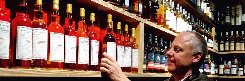Frank Jerger vor einem Whisky-Regal in seinem Laden.