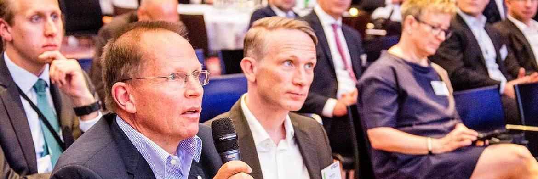Ulrich Welzel von Brainactive (l.) stellt eine Frage zum Fintech-Vortrag von Frank Schwab, rechts daneben Jürgen Kob von Friends & Finance|© C. Scholtysik / P. Hipp