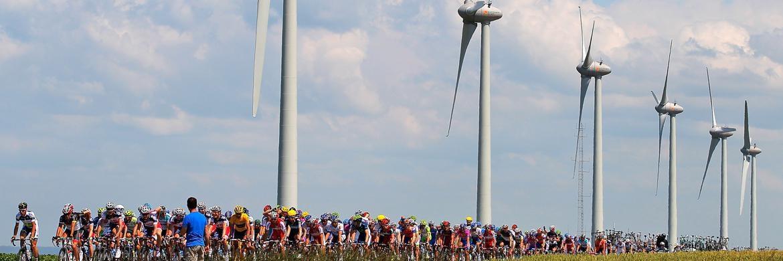 Radrennen vor Windturbinen in Frankreich. Anlegen unter Nachhaltigkeitsgesichtspunkten ist auch gut für die Rendite, hat eine Studie von SSGAergeben.