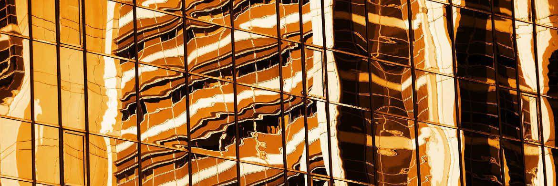 Verschwommene Spiegelungen in einer Bürohausfassade: 2018 wechselt die Besteuerung von Immobilienfonds von transparent auf intransparent.|© Pixabay