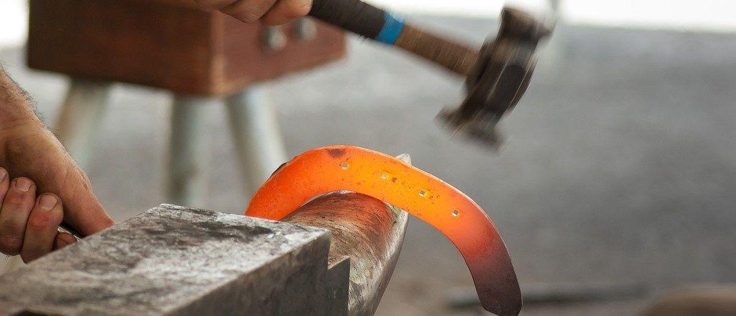 Ein Mann am Amboss mit Hammer und Hufeisen: Im vorliegenden Fall konnte der Mann nicht länger als Hufschmied arbeiten.|© Pixabay
