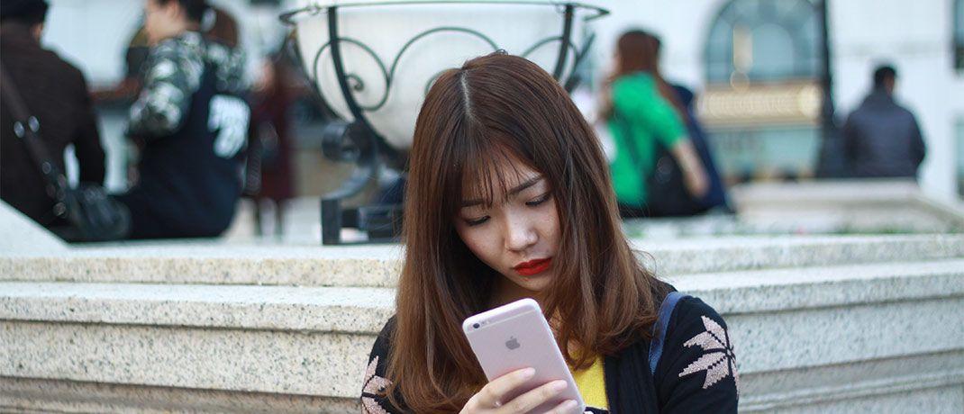 Chinesin mit Smartphone: IT-Unternehmen aus den Schwellenländern sind im Templeton Emerging Markets Balanced Fund derzeit hoch gewichtet.
