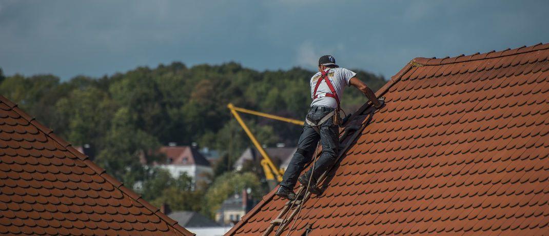 Ein Dachdecker verlegt Dachziegeln auf einem Hausdach: Für Menschen mit gefährlichen Berufen, wie eben Dachdecker, ist eine Berufsunfähigkeitsversicherung oft unbezahlbar.|© Pixabay