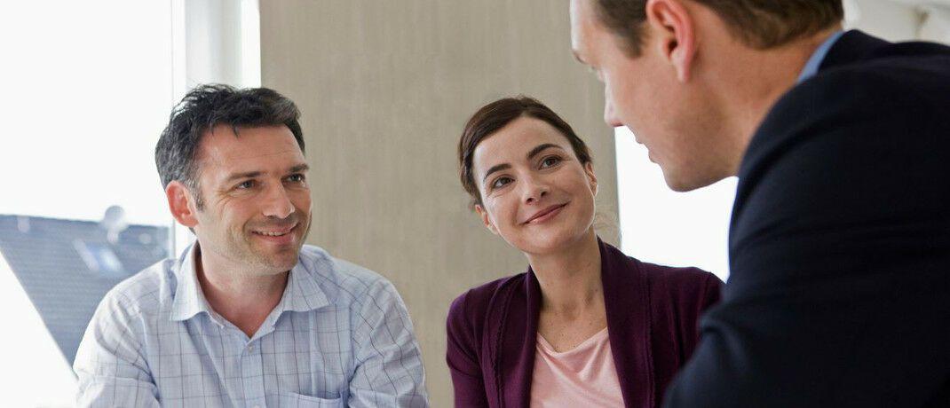 Finanzberater im Gespräch mit Kunden. DAS INVESTMENT hat die wichtigsten Informationen zur neuen DIN-Norm 77230 aus Beratersicht zusammengestellt.|© Axa
