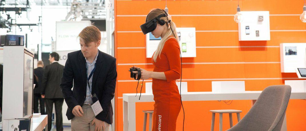 Eine Frau testet das Bezahlen per Virtual-Reality-Brille an einem Wirecard-Messestand: Die Aktie des jüngsten Dax-Unternehmens mit Sitz in Aschheim bei München verzeichnete in den vergangenen zwölf Monaten heftige Ausschläge. Der Kurs schwankte zwischen 199 und 86 Euro. |© Wirecard AG