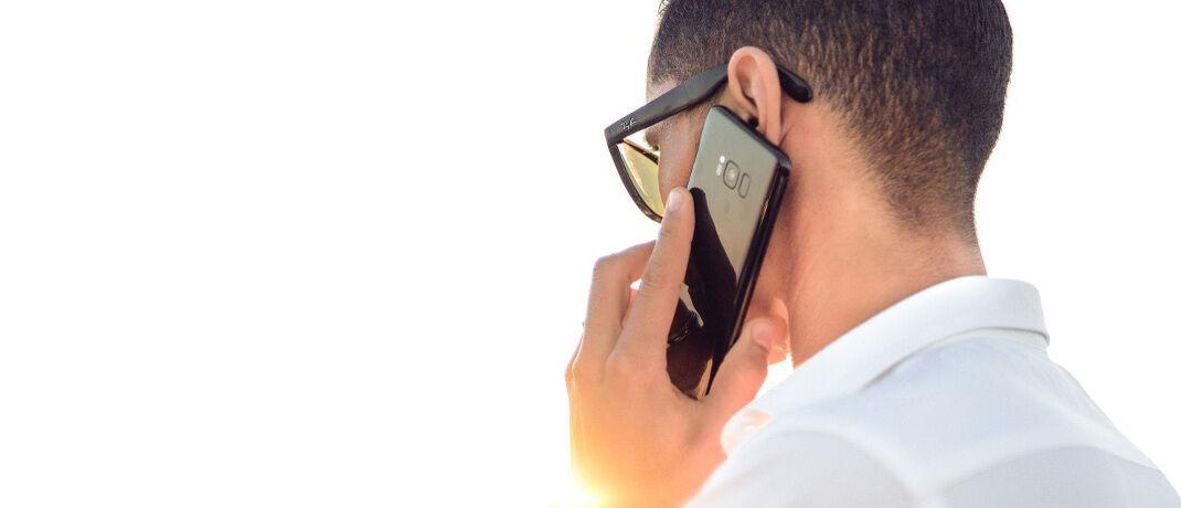 Mann mit Smartphone: Das OLG Düsseldorf hat entschieden, wann ein Versicherungsmakler Kunden telefonisch kontaktieren darf.