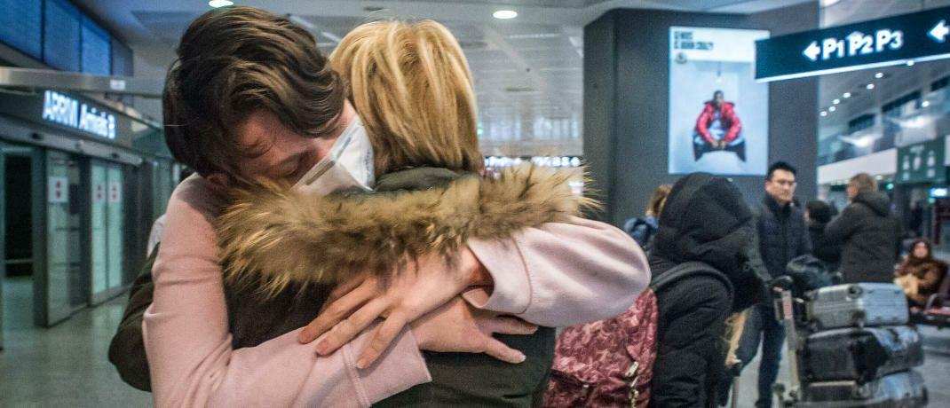 Reisende mit Mundschutz kommen aus China in Mailand an: Der Coronavirus lässt die Börsen derzeit zittern.|© imago images/Carlo Cozzoli