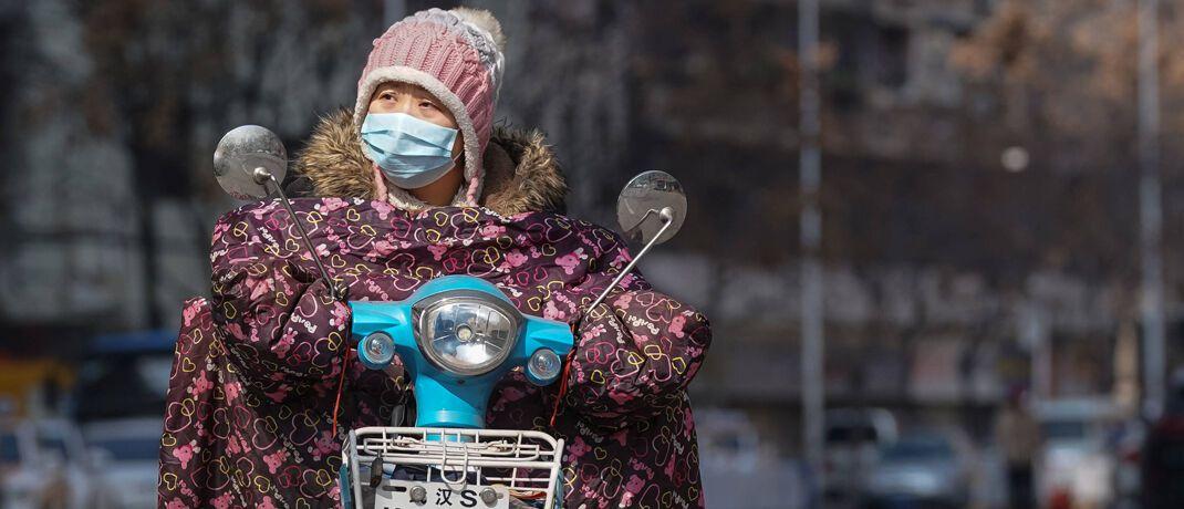 Frau mit Mundschutz: Ursprünglich brach das Coronavirus in der Stadt Wuhan aus.|© imago images / Xinhua