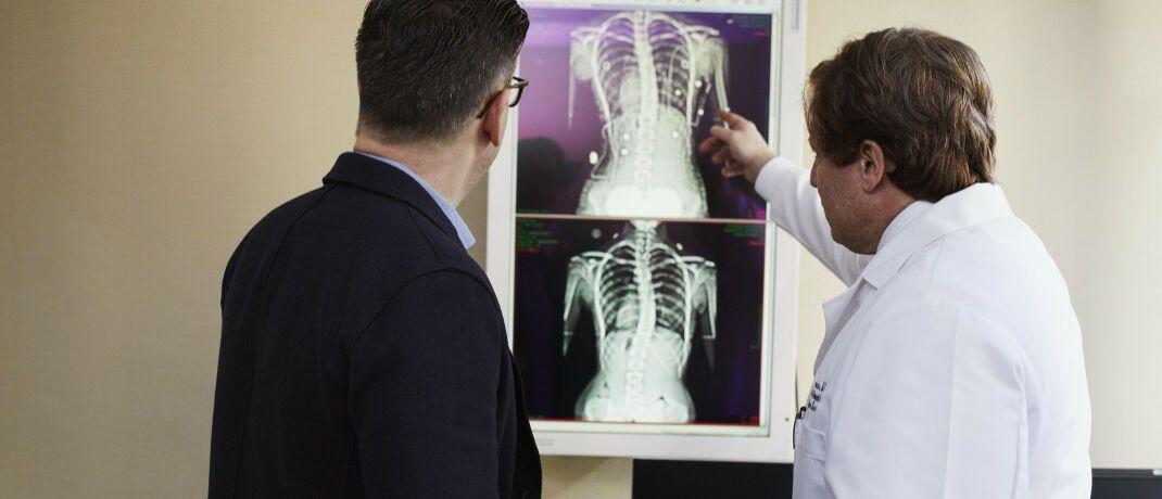 Arzt zeigt dem Patienten die Röntgenaufnahme seines Rückens: GKV-Versicherte haben häufiger Erkrankungen wie Diabetes, Depressionen, Gelenkerkrankungen und chronische Rückenbeschwerden.|© Pexels