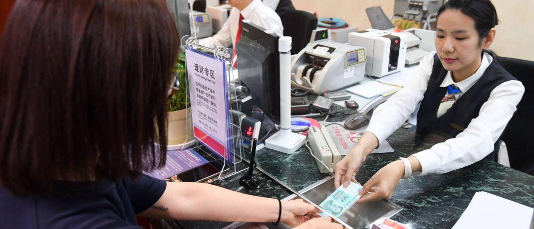 Kasse in einer Filiale der Industrial and Commercial Bank of China (ICBC) in der chinesischen Hauptstadt Peking: Bargeld geht sprichwörtlich durch viele Hände und könnte damit den Virus Covid-19 übertragen.|© imago images / Xinhua