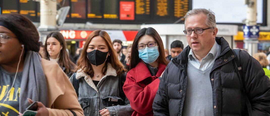 Reisende mit Schutzmaske: Internationale Versicherer wie Zurich vermeiden aktuell Flüge zu Konzerntöchtern im Ausland und führen stattdessen Videokonferenzen durch.|© imago images / ZUMA Press