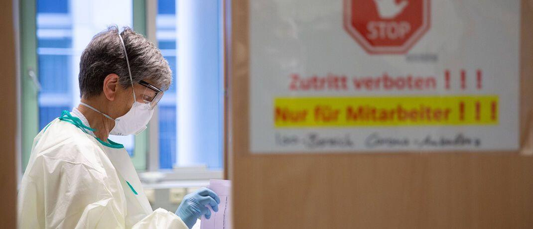 Eine Mitarbeiterin des Klinikums Stuttgart bereitet die Aufnahme von Corona-Patienten vor: Der Virus schadet der Weltwirtschaft.