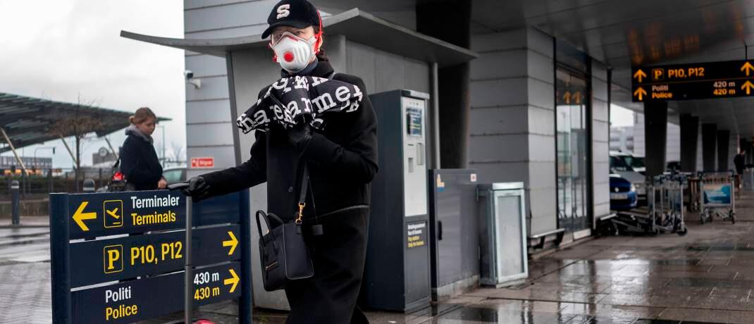 Frau mit Atemschutz am Flughafen Kopenhagen: Nach Ansicht der Danske Bank könnte sich die Konjunktur schon in der zweiten Jahreshälfte 2020 wieder erholen. © imago images / Ritzau Scanpix