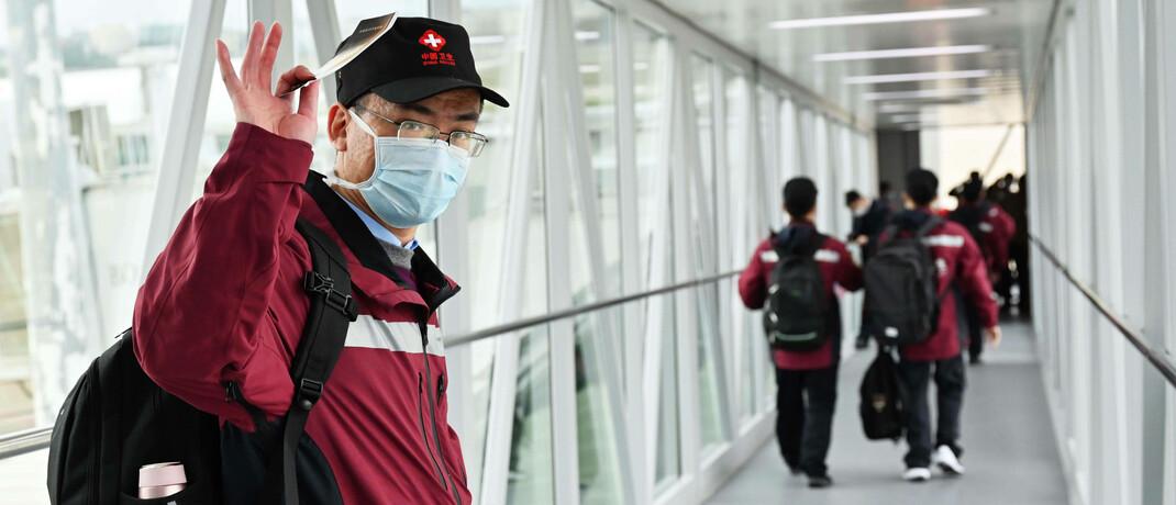 Corona-Spezialisten auf dem Weg zu einem Flugzeug, das sie vom chinesischen Fuzhou nach Italien bringen soll: In China ebbt die Corona-Welle bereits wieder ab.|© imago images / Xinhua / Wei Peiquan