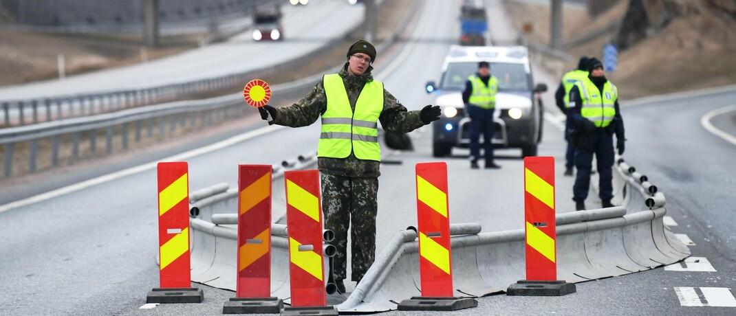 Polizei und Soldaten sperren im finnische Lohja eine Straße, um die Corona-Pandemie einzudämmen: Als Reaktion auf die Corona-Krise verzeichnen die Märkte stark schwankende Kurse.|© imago images / Lehtikuva