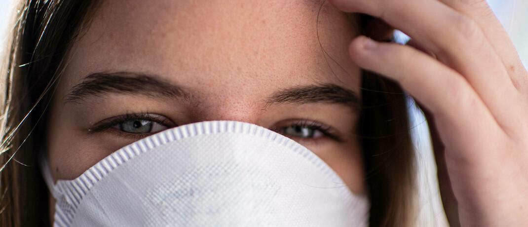 Frau mit Mundschutz: Gutverdiener, die aufgrund der Corona-Krise in Kurzarbeit gehen und dadurch unter die  Jahresarbeitsentgeltgrenze rutschen, bleiben trotzdem in der PKV.|© imago images / Noah Wedel