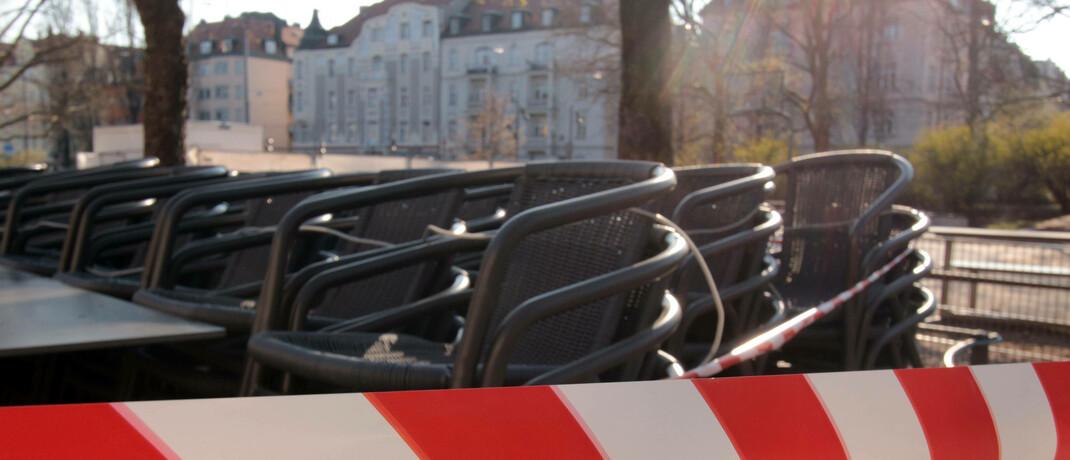 Mit Absperrband versperrter Außenbereich eines Cafés in München Schwabing: Hotels und Restaurants in Bayern, die eine Betriebsschließungsversicherung haben, bekommen bis zu 15 Prozent der vereinbarten Tagessätze erstattet.|© imago images / Ralph Peters