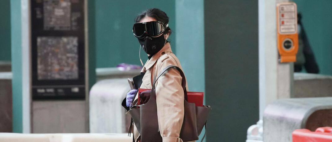 Passantin mit Schutzkleidung: Die wirtschaftlichen Probleme durch die Corona-Pandemie will die Regierung mit weitreichenden Maßnahmen mildern © imago images / UPI Photo