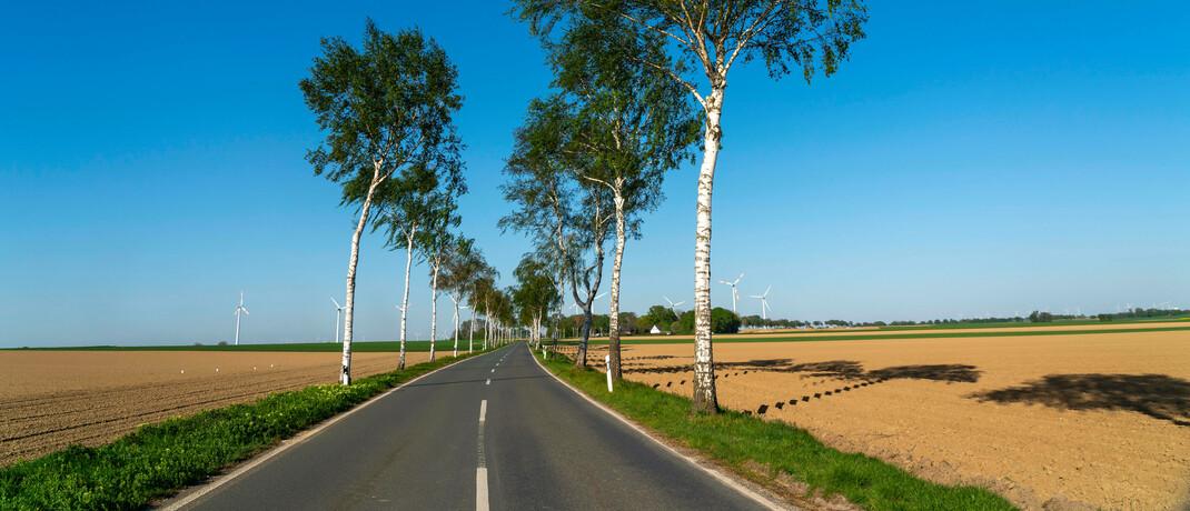 Landstraße und Windräder: Helvetia unterstützt als Investor unter anderem den Bau von Windkraftanlagen © imago images / Jochen Tack