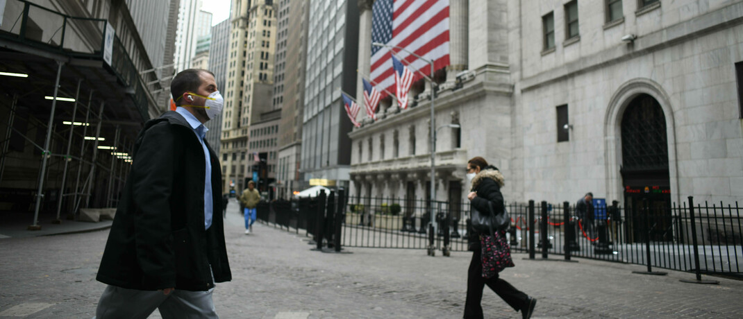 Passanten mit Schutzmasken in der Wall Street in New York: Nach massiven Kurseinbrüchen haben sich die Aktienmärkte wieder etwas erholt, sind aber von ihren Höchstständen weit entfernt.|© imago images / ZUMA Wire