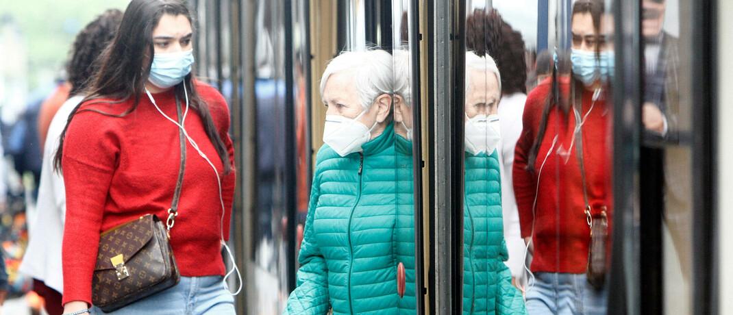 Menschen mit Mundschutz an einer Straßenbahnhaltestelle in Mannheim: Die Corona-Pandemie hat auch die Kapitalmärkte einbrechen lassen.