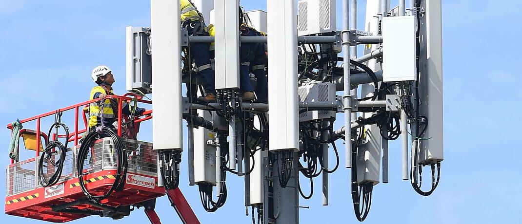 Arbeiter bauen an einer 5G-Funkzelle, einer Anlage, die Mobilfunksignale ver- und entschlüsselt.|© imago images / AAP / Dan Himbrechts