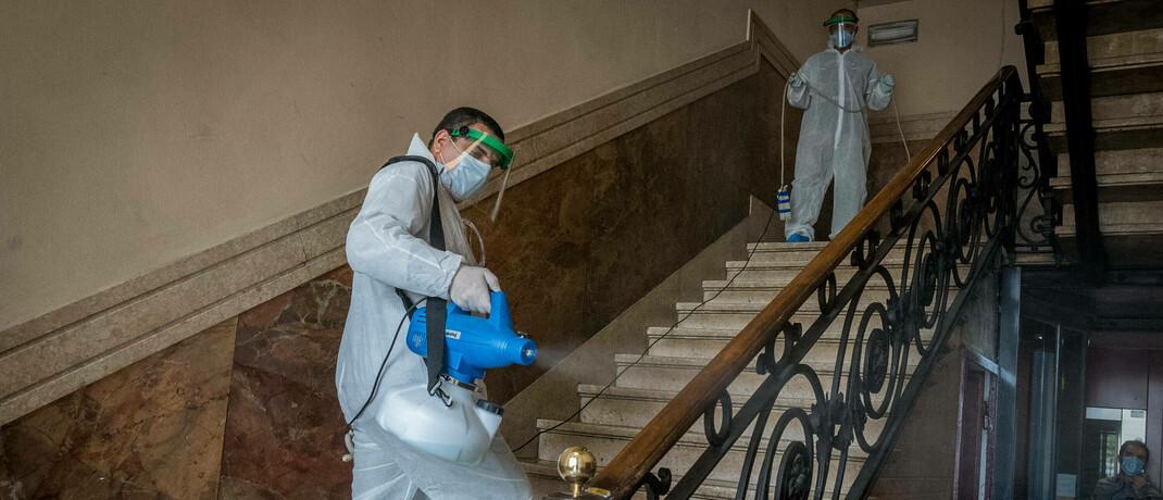 Reinigungskräfte desinfizieren ein Treppenhaus in Mailand: Die Corona-Krise hat für Kurseinbrüche und weiterhin unruhige Märkte gesorgt.  © imago images / Independent Photo