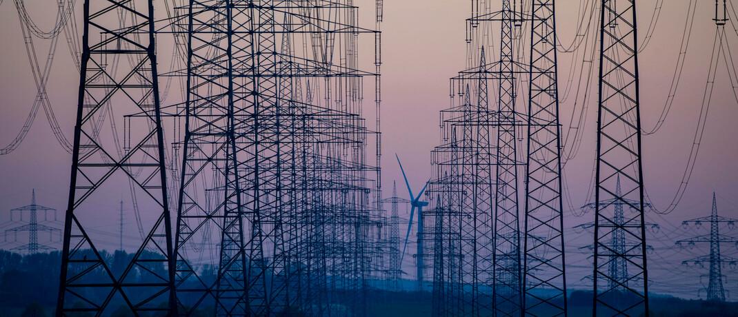 Hochspannungsleitungen vor einem Windrad. Lieferengpässe und Unsicherheit am Markt könnten den Umstieg zu erneuerbaren Energien verzögern.