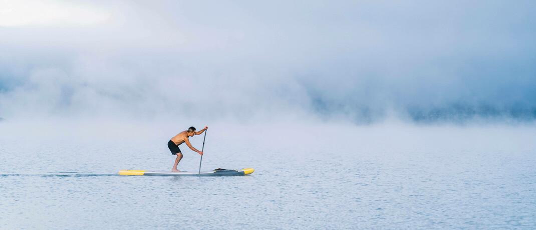 Stehpaddler auf einem See im Nebel: Auch auf den Finanzmärkten ist die Vorhersehbarkeit derzeit eingeschränkt, meint Edmond de Rothschild Asset Management.