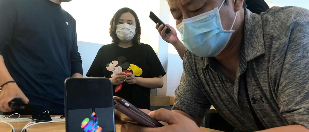 Mann bedient iPhone in einem Apple-Store in Peking: Reichen zwei bis drei Monate Corona-Lockdown aus, damit sich das Kaufverhalten der Verbraucher nachhaltig verändert?