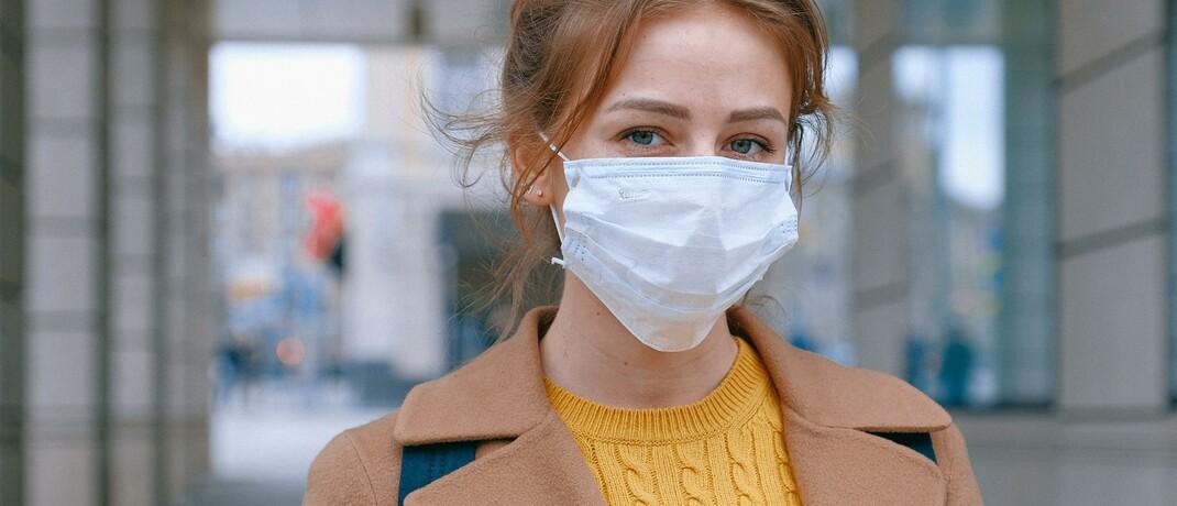 Frau mit Atemschutzmaske: Die Corona-Pandemie könnte zu höheren Versicherungsprämien führen.
